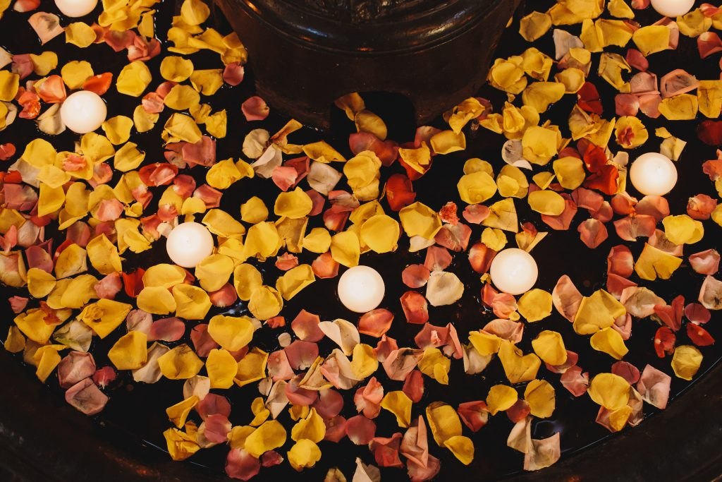 Look from above at white burning candles floating between the petals